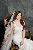 Fashion interior photo of beautiful bride with blond hair in elegant wedding dress