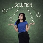 picture of solution  - Young businesswoman with options of solution and confuse to choose one of the solutions - JPG