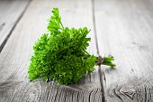 stock photo of tied  - tied fresh green parsley on wooden surface - JPG
