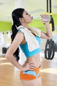 Fit Woman Drinking Water At Gym