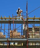 Constructrion site - scaffold and worker in action