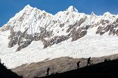 foto of andes  - Hikers silhouetted against the Cordillera Blanca part of the Andes mountains near Huaraz Peru - JPG