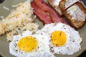 picture of hash  - Eggs sunny side up with hash browns bacon strips and banana bread for breakfast - JPG