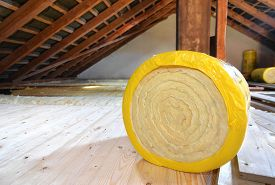 stock photo of rafters  - A roll of insulating glass wool on an attic floor  - JPG