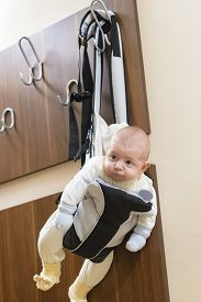 foto of laughable  - Cute baby sitting in a front baby carrier - JPG