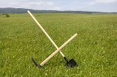 foto of grassland  - Work tools pickaxe and shovel crossed and stuck in a green rural grassland - JPG