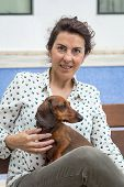 stock photo of dachshund dog  - A Attractive woman playing with dachshund dog - JPG