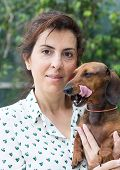 pic of dachshund dog  - A Attractive woman playing with dachshund dog - JPG