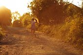 stock photo of beatitudes  - Small happy little girl running along a country road - JPG