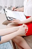 picture of woman red blouse  - Close up photo of hands of a woman sitting on a couch and a psychologist sitting in an armchair - JPG
