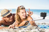 stock photo of selfie  - Happy couple taking selfie with selfie stick at the beach - JPG