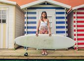 picture of beach hut  - Portrait of beautiful young surfer woman with white top and bikini holding surfboard over a beach striped huts background - JPG