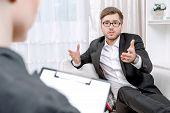 stock photo of psychologist  - Young man wearing a black suit sitting on a couch telling his problems and gesticulating - JPG