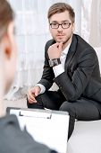 pic of psychologist  - Young man wearing a black suit sitting on a couch looking at his doctor and listening - JPG