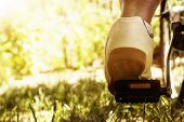 foto of pedal  - shoe on the bike pedal in front of bloomy sunny nature background
