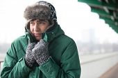 image of shivering  - Man in warm clothing shivering outdoors - JPG