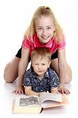 foto of little sister  - Big sister and little brother reading a book lying on the floor - JPG