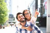 stock photo of piggyback ride  - Cheerful woman pointing away while enjoying piggyback ride on man in city - JPG