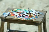 stock photo of paint palette  - Wooden stand with palette and paint on beach - JPG