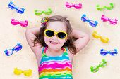 foto of protective eyewear  - Child wearing sunglasses on a beach - JPG