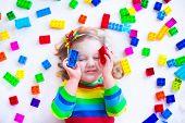 stock photo of preschool  - Preschooler child playing with colorful toy blocks - JPG
