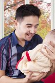 image of happy baby boy  - Portrait of happy young dad holding his baby boy and smiling on the baby at home shot with autumn background on the window - JPG