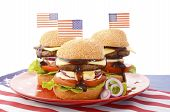 stock photo of bbq party  - The Great BBQ Hamburger with American flags for USA Fourth of July and holiday events party celebrations - JPG