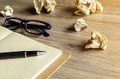 image of stress-ball  - Crumpled paper balls with eye glasses and notebook on wood desk with soft light - JPG