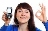 foto of diabetes  - Smiling woman holding glucose meter measuring sugar level concept for diabetes - JPG