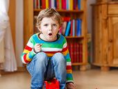 stock photo of daycare  - Funny blond kid boy shouting and playing indoors - JPG