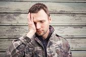 pic of camouflage  - Young Caucasian man with headache in camouflage - JPG