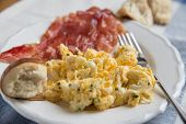 stock photo of scrambled eggs  - Scrambled eggs with bacon and bread for breakfast  - JPG