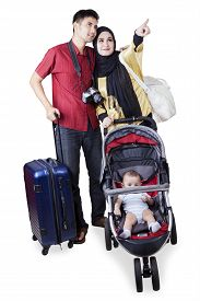 foto of muslim man  - Portrait of two muslim parents travelling together while carrying their baby on the pram - JPG