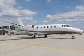 picture of cloudy  - Aircraft learjet Plane in front of the Airport with cloudy sky and sun - JPG