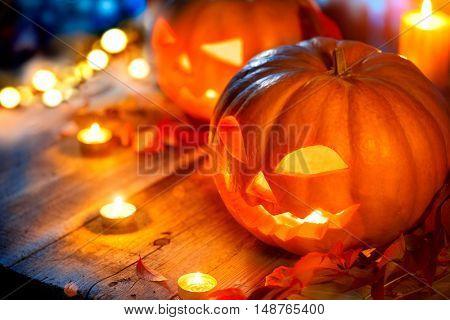 Halloween pumpkin head jack lantern with burning candles over wooden background. Halloween holidays