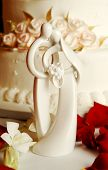 Bride and Groom cake toppers in front of a soft white wedding cake with floral accents