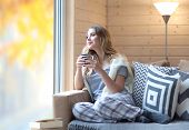 Young beautiful blonde woman with cup of coffee sitting home by the window. Autumn fall trees reflec poster