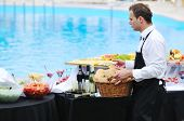 foto of buffet catering  - young people serving food on buffet wedding seminar or conference outdoor party with fresh food and drink - JPG