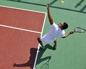 joven jugar tenis al aire libre en tenis naranja de temprano en la mañana