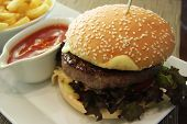 Fancy cheeseburger with french fries and sauce