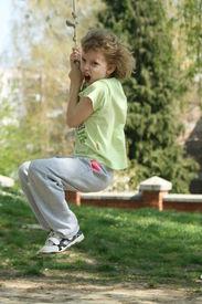 image of tarzan  - A young girl playing Tarzan in the playground - JPG