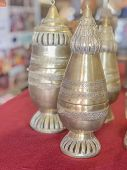Brass Handicrafts Of Various Types, Placed On A Table Covered With A Red Cloth. poster