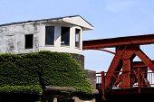 foto of gatekeeper  - Old drawbridge gatehouse covered with ivy by bridge - JPG