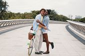 Side View Of Embracing Black Woman And Man Standing With Bicycle On Bridge And Embracing In Love poster