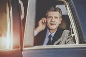 Handsome Businessman In Car Talking On Smartphone. Man In Black Suit Sitting In Car. Handsome Man In poster