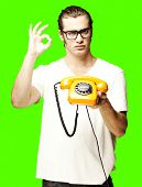 portrait of young man holding a vintage telephone against a removable chroma key background