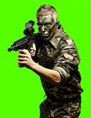 portrait of soldier aiming with gun against a removable chroma key background