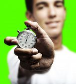 young man pushing a stopwatch button against a removable chroma key background