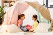 childhood, hygge and friendship concept - little girls talking in kids tent or teepee at home poster