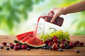 healthy eating, food, dieting and vegetarian concept - hand pouring fruit and berry juice or smoothi poster